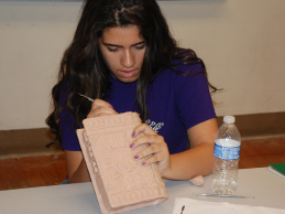 After covering her book with Super Sculpey, she is carving the designs onto her book.