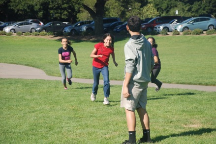 Scholars enjoying a game of tag on the grassy quad at Stanford University.