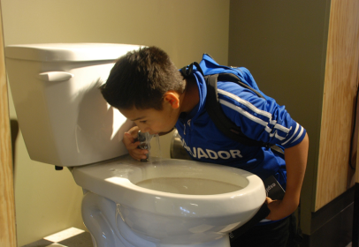 A scholar is bold enough to drink from one of the interesting water fountains at The Exploratorium.