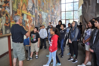 The curator, William Maynez, tells the scholars about the stories within the Diego Rivera Mural.