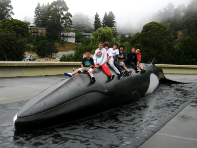 Scholars sitting on a whale located outside of the Lawrence Hall Science in Berkeley.