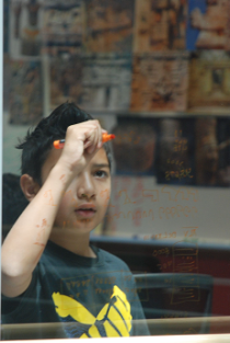 This scholar practices mayan mathematics on glass walls at Stanford University.