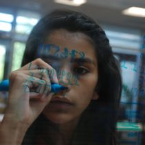 This scholar practices the Egyptian numerical system on the glass walls at Stanford University.