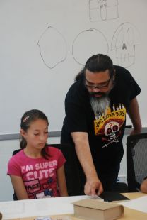 Artist and production designer Simon Varela, helps a scholar with the Mayan Book Project at Stanford University.