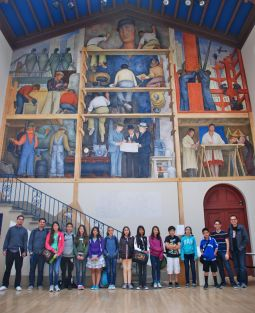 """DaVinci Camp scholars and staff pose in front of Diego Rivera's """"Making a Fresco"""" at the San Francisco Art Institute."""