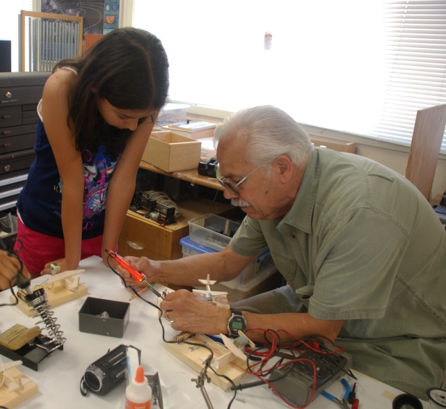 This scholar gets help on her airplane project by Dr. George Castro during his science workshop in San Jose.