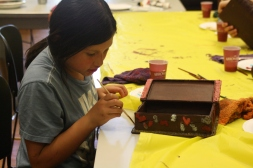 A scholar painting all the little details on her book. What cool shapes!