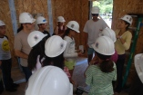 Scholars learn about the competition for the most innovative solar home, while touring Stanford's own solar home model.