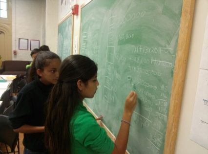 A scholar observes her peer working with the Mayan number system.