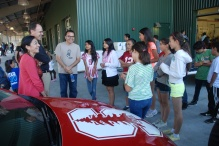 Professor of Mechanical Engineering at Stanford University talks with the scholars as they visit the unveiling of the solar car.