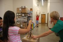 A scholar using the trebuchet at E&M labs to try and launch a marble through the ring!