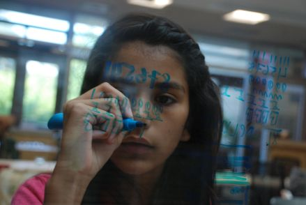 This scholar is focusing on practicing the different numeral systems on the glass walls at Stanford University.