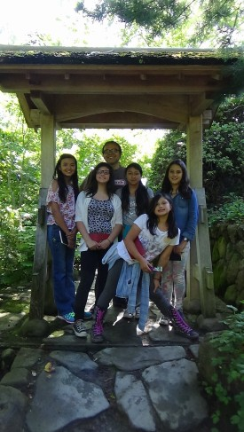 DaVinci camp staff member and campers smile for a photo as they escape the heat on this shady path