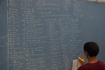 A scholar working hard and filling up the chalkboard with polynomials.
