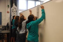 Scholars practice their factorization on white boards directly next to their peers so they can check each others work.