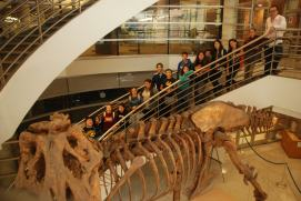 DaVinci Camp posing next to the Tyrannosaurus Rex cast found in the VLSB at UC Berkeley.