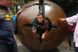"The smile of a scholar as she finishes crawling through Arnaldo Pomodoro's ""Sphere within Sphere"" at UC Berkeley"