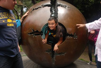 """The smile of a scholar as she finishes crawling through Arnaldo Pomodoro's """"Sphere within Sphere"""" at UC Berkeley"""