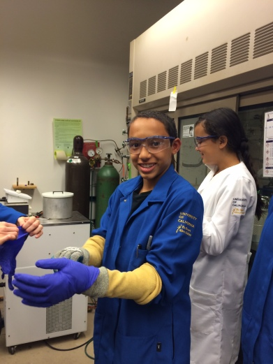 This scholar is putting on the protective gloves needed while working with chemicals in a vacuum chamber.