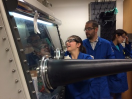 This scholar practices reaching into an argon filled chamber in the lab through the protruding rubber gloves.