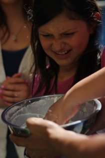 This camper struggles to take her hand out of the non-Newtonian fluid made with cornstarch and water.
