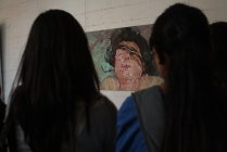 The scholars examine the art along the walls of the San Francisco Art Institute.