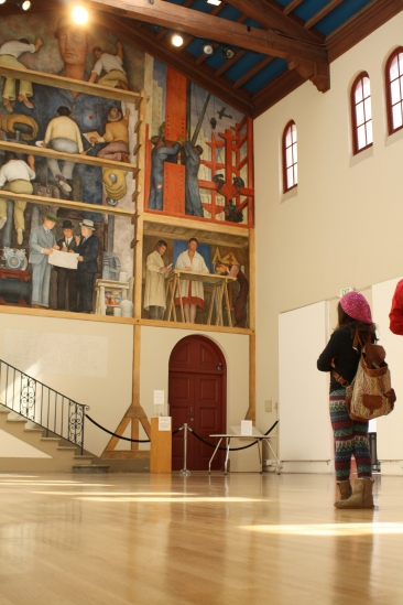 """A young scholar is captivated by the intricate beauty of Diego Rivera's """"The Making of a Fresco."""""""