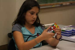 The face of a concentrated camper as she learns to solve the Rubiks Cube. She is remembering the up up down down left inverted right right algorithm.