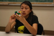 A scholar planning her next move as she works on solving her rubiks cube