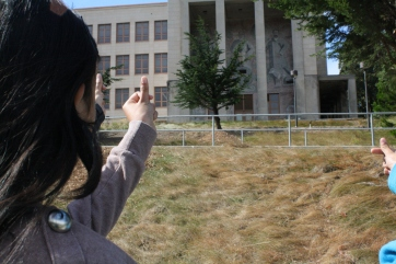 This scholar estimates the measurement of the building's height using her thumb as a reference.