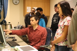 Scholars and staff observe data (brain cross sections) recorded by an MRI machine.