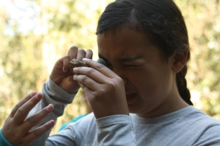 This DaVinci Camp scholar looks through this magnifying instrument called a loupe to describe the details found in a piece of sedimentary rock called Claremont.