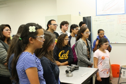 Scholars watch as a machine in the basement of the mechanical engineering building stretches a bar of a synthetic polymer until it breaks.