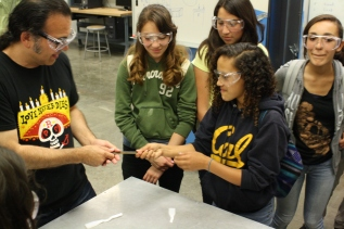 DaVinci camp staff member and camper test the strength of a steel bar by attempting to stretch it by pulling on both sides of it