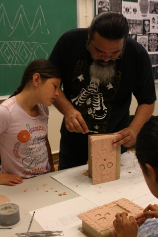 Artist and production designer, Simon Varela shows this scholar a technique to mold the super sculpy on the side of her box
