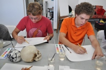 Two students begin sketching out their paintings during an art workshop.
