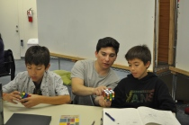An instructor teaches a young DaVinci how to solve the Rubik's Cube.